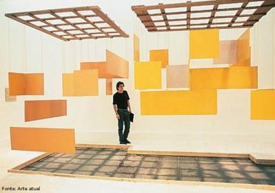 Hélio Oiticica (1937/1980), carioca, foi pintor, escultor e performático brasileiro. É considerado um dos artistas mais revolucionários de seu tempo e sua obra experimental e inovadora é reconhecida internacionalmente. Foi um dos fundadores do Grupo Neoconcreto, em 1959. Nesse mesmo ano, o artista marca o início da transição da tela para o espaço ambiental. Em 1960, cria os primeiros Núcleos, também denominados Manifestações Ambientais e Penetráveis, placas de madeira pintadas com cores quentes penduradas no teto por fios de nylon. Neles tanto o deslocamento do espectador quanto a movimentação das placas passam a integrar a experiência.