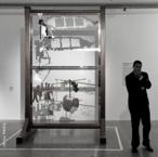 Marcel Duchamp (França, 1889-1968), um dos precursores da arte conceitual. Tendo se mudado para Nova York e largado a Europa, Duchamp encontra na América um solo fértil para sua arte dadaísta. Decorrente dessa fase, nasce o projeto para a obra mais complexa do artista: A noiva despida pelos seus celibatários, mesmo ou O grande vidro. Trata-se de duas lâminas de vidro, uma sobre a outra, onde se vê uma figura abstrata na parte de cima, que seria a noiva, e na parte de baixo, se percebe uma porção de outras figuras (feitas de cabides, tecido e outros materiais), dispostas em círculo, ao lado de uma engrenagem (retirada de um moinho de café). Não se tem um consenso acerca do que representa essa obra, mas diversas opiniões conflitantes que ainda rendem bastante discussão. Como observou Octavio Paz, o Grande Vidro &lsaquo;é um enigma e, como todos os enigmas, não é algo que se contempla mas sim que se decifra&rsaquo;. <br/> Palavras-chave: Marcel Duchamp, arte conceitual, arte dadaísta, Noiva Despida, Grande Vidro